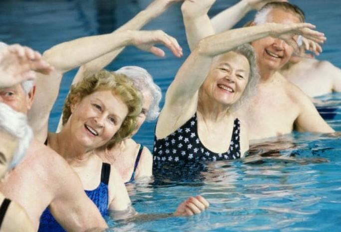 Personas de tercera edad haciendo deporte en el agua, aquafitness